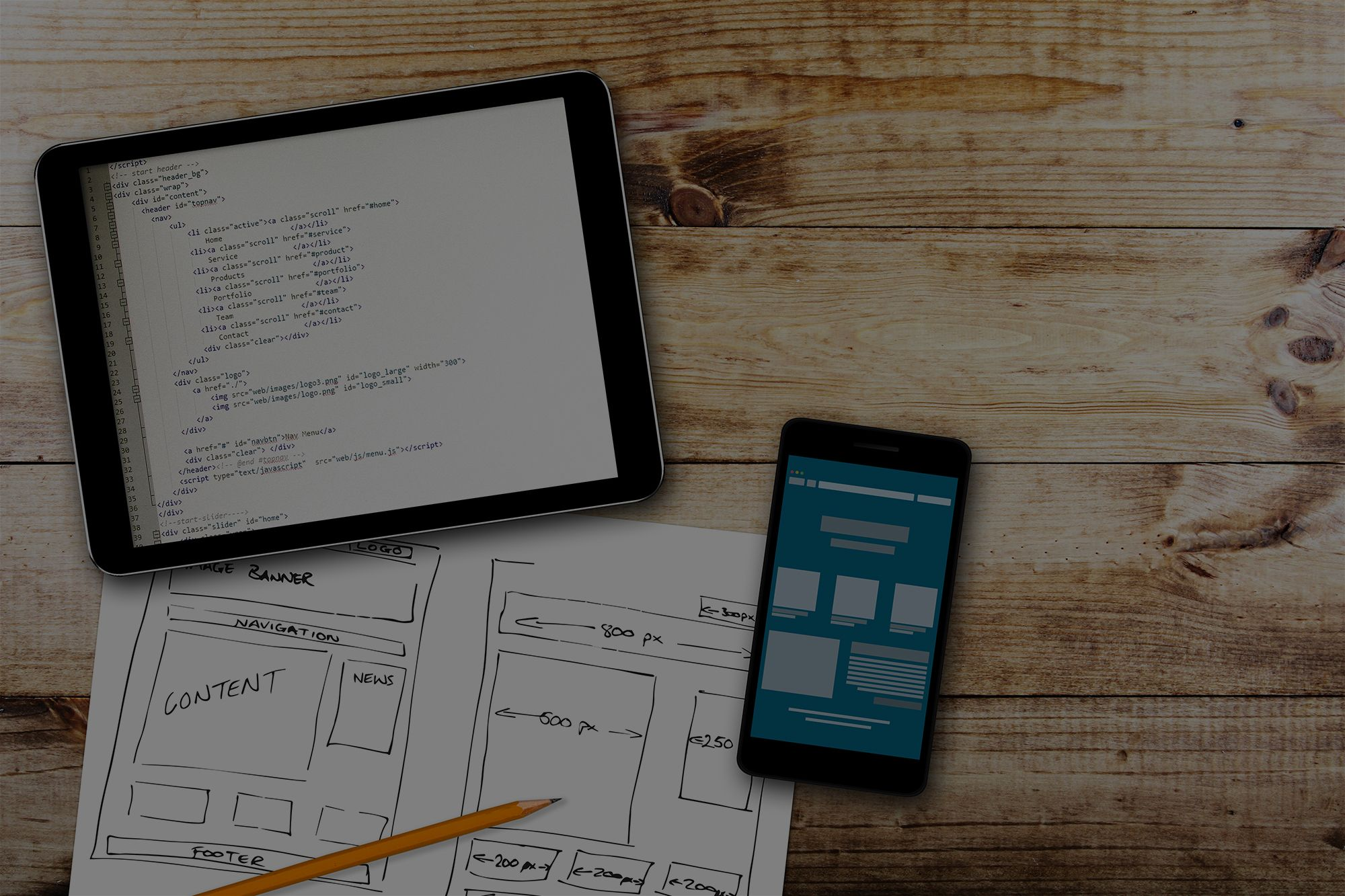 trueITpros website wireframe sketch and programming code on digital tablet